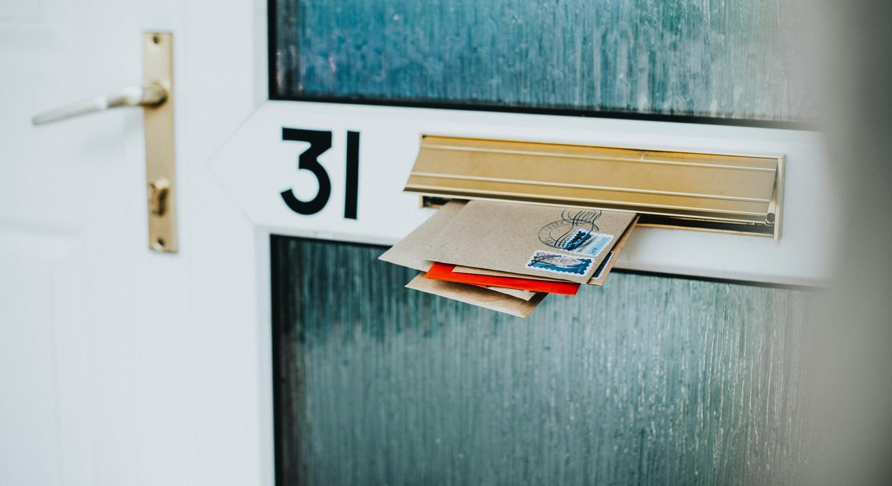 envelops in mail slot on door